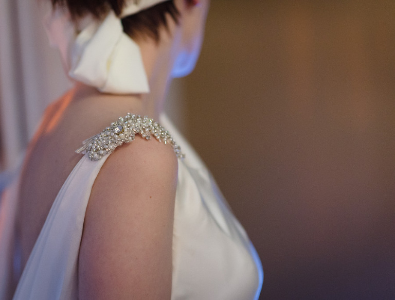 a cut-off photograph of a bride wearing an ivory silk wedding dress with pearl and crystal beading on the shoulder