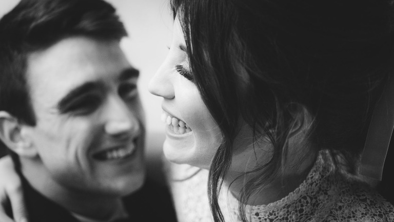 A black and white photograph of a young couple laughing in a natural wedding photography style