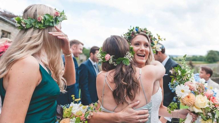 natural wedding photograph at broughton hall of bride hugging bridesmaid