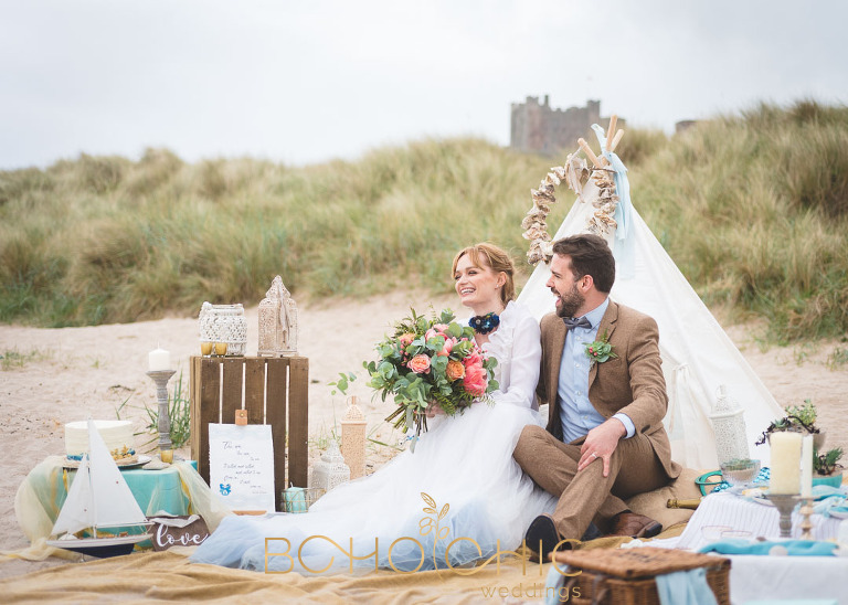 natural wedding photograph on bamburgh beach in northumberland with bamburgh castle in the background
