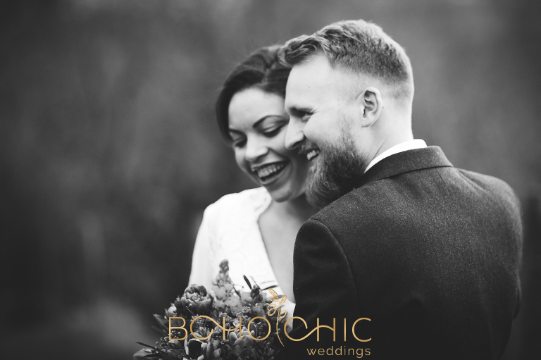 black and white natural wedding photograph of a young very in love couple laughing together by yorkshire photographer Catherine