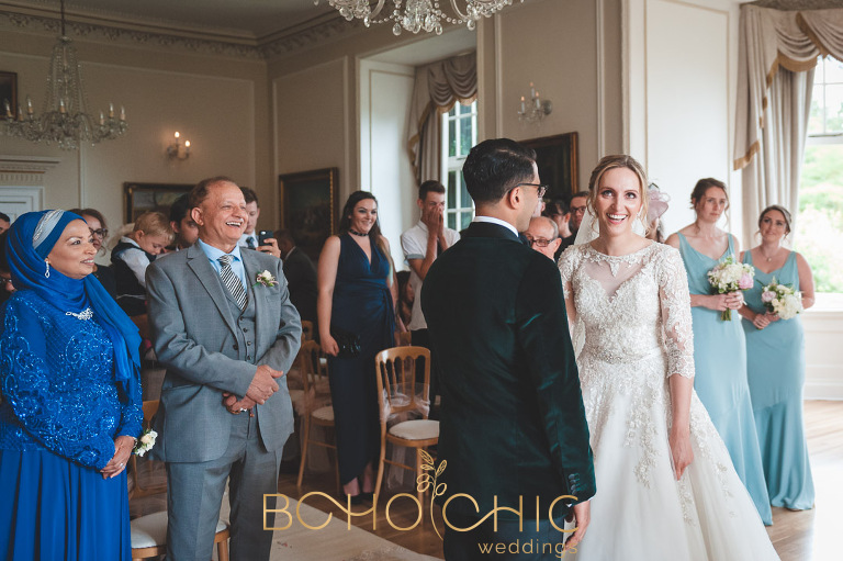 smiling bride and groom with wedding guests in the ceremony room at Goldsborough Hall