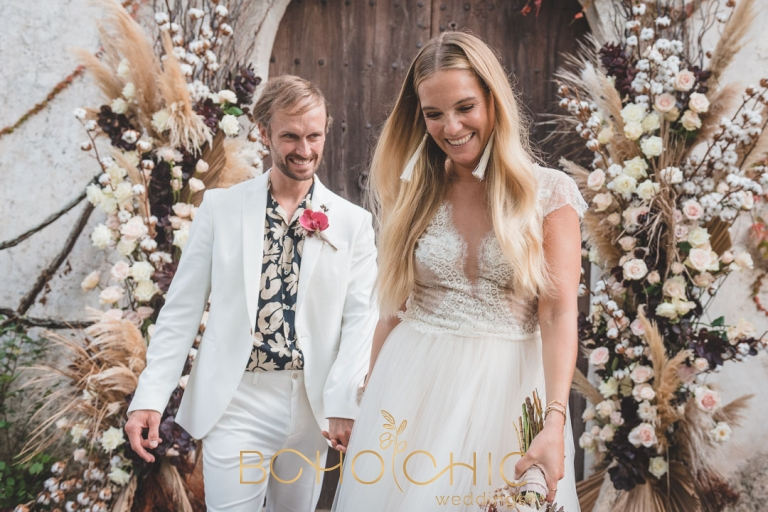 destination wedding photography in mallorca showing a beautiful couple by a doorway surrounded by autumnal flowers at fangar finca