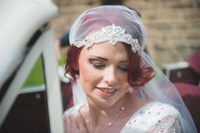 bride dressed in art deco style wedding dress wand head dress at East Riddlesden hall in yorkshire
