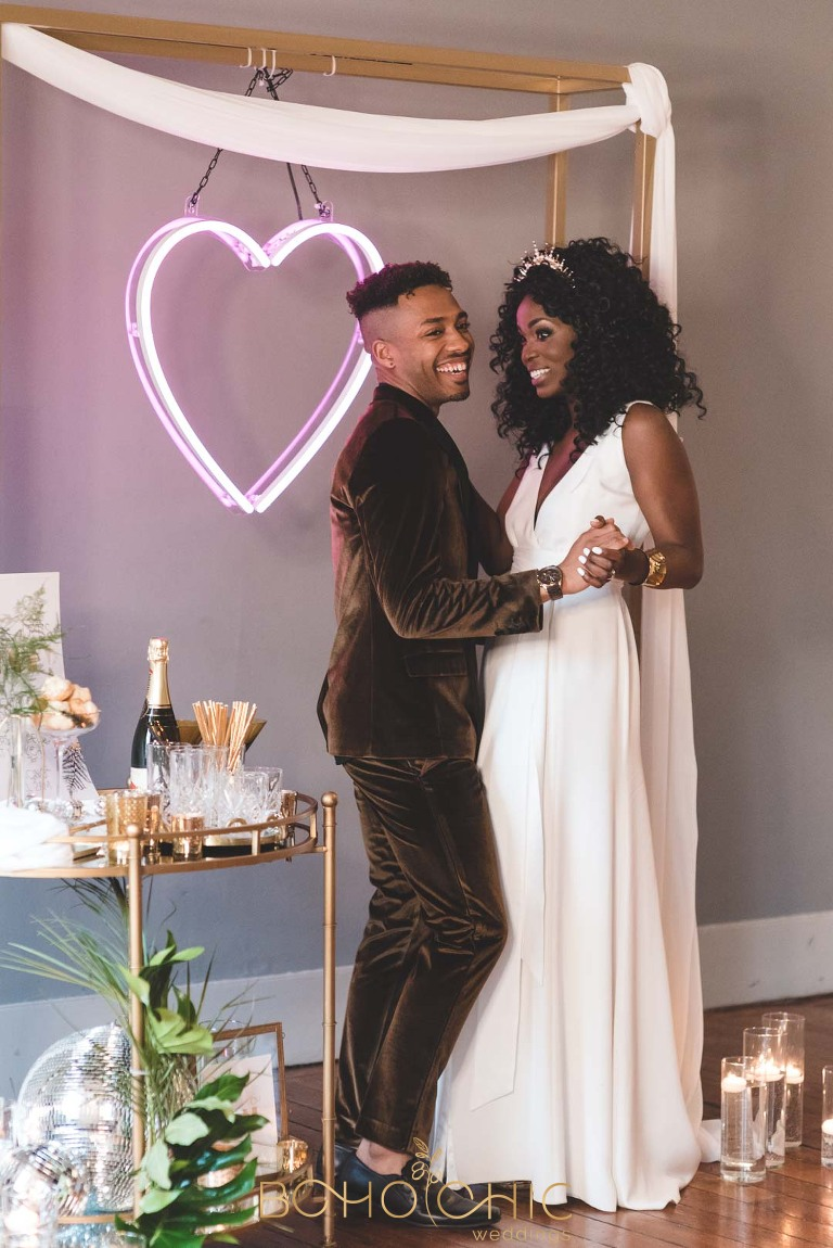 african bride wearing the charlie brear wedding jumpsuit Carson with groom wearing a velvet suit from River Island