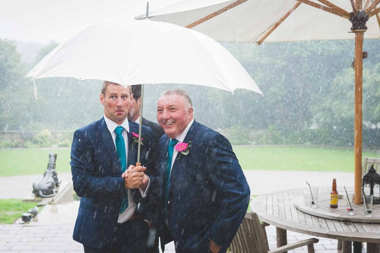 wedding photograph of the best man and the grooms dad sheltering under an umbrella while it pours with rain at the Woodlands Hotel in Leeds