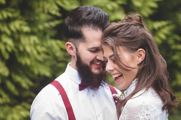 a very natural photograph of a young, stylish bride and groom laughing together at Camp Kaur in North Yorkshire