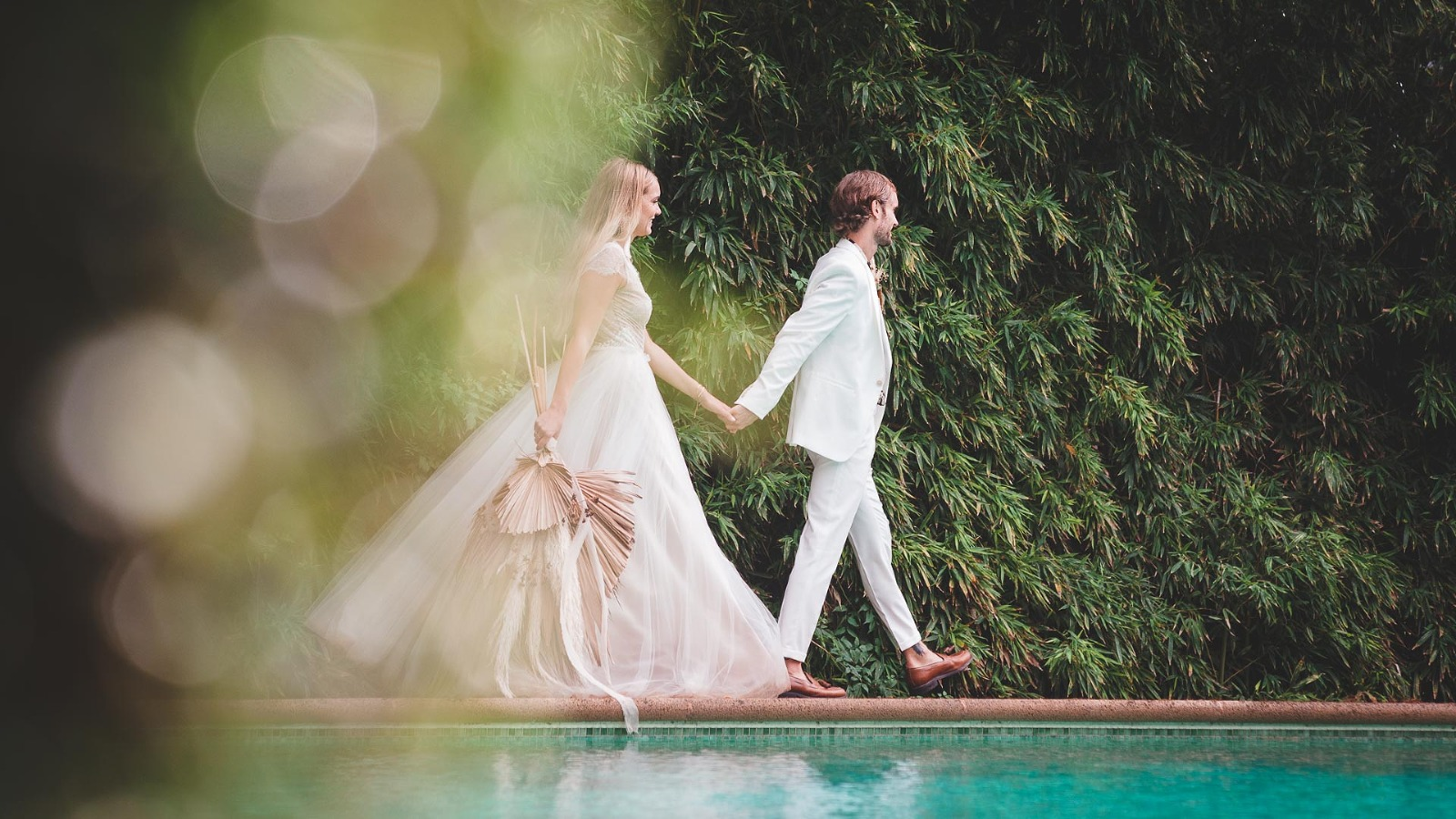 a natural wedding photograph by award winning yorkshire wedding photographer of a couple by the pool