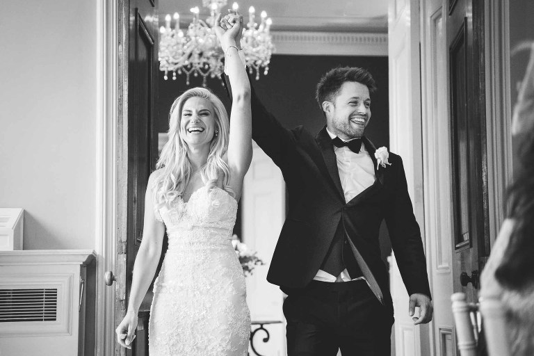 a very chic fashionable couple lifting their arms in joy when entering their wedding breakfast room to the applause of their guests