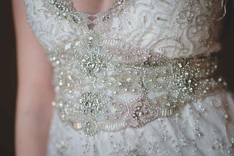 close up colour photograph of the exquisite beading on an Anna Morgan silk wedding dress