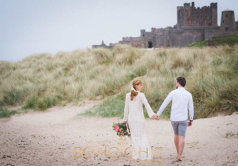 colour photograph taken at Bamburgh beach of a couple in Bohemian wedding outfits
