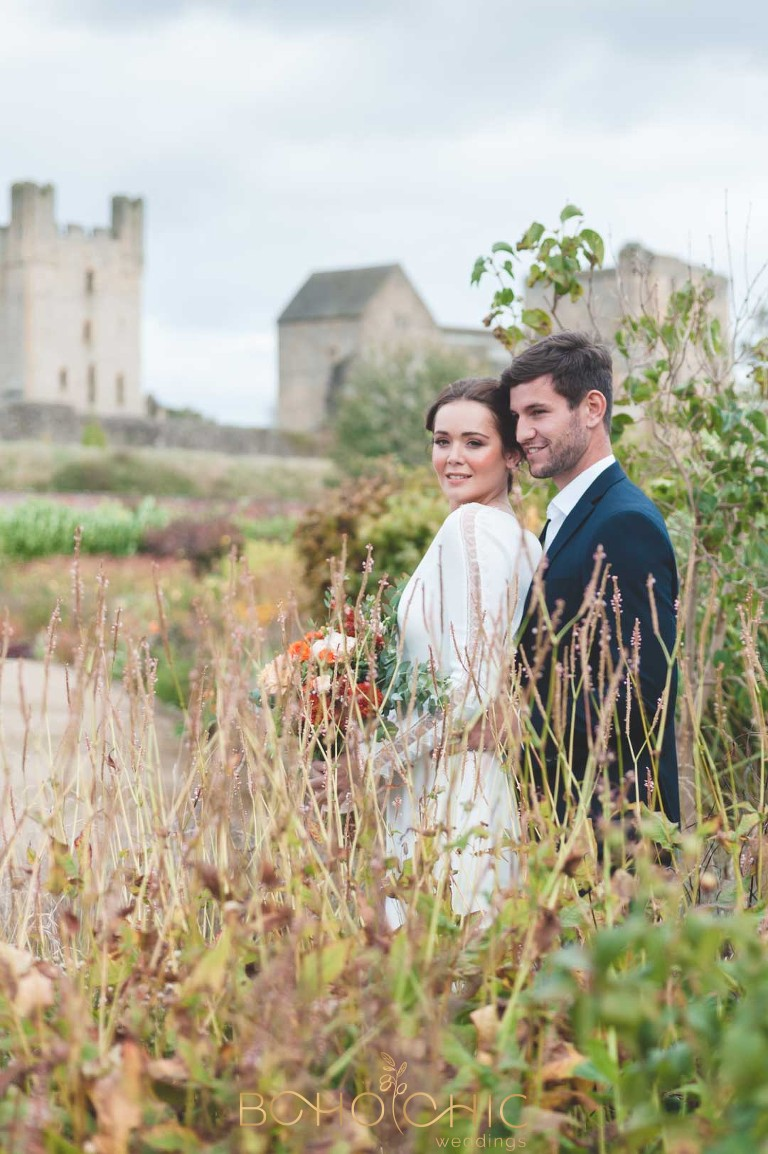 Colour photograph of a beautiful brunette couple in helmsley walled garden in the autumn with helmsley castle in the background. Wedding Photography in Yorkshire by professional photographer, Catherine