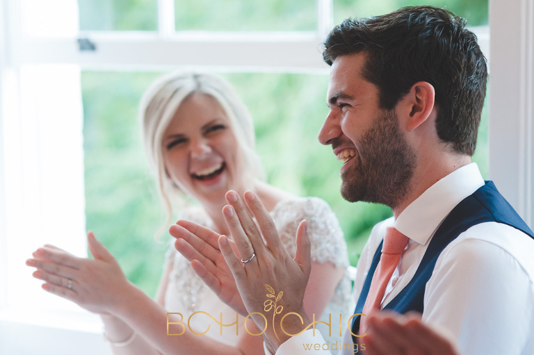 colour photograph of a couple laughing at their wedding speeches eat a wedding venue in surrey