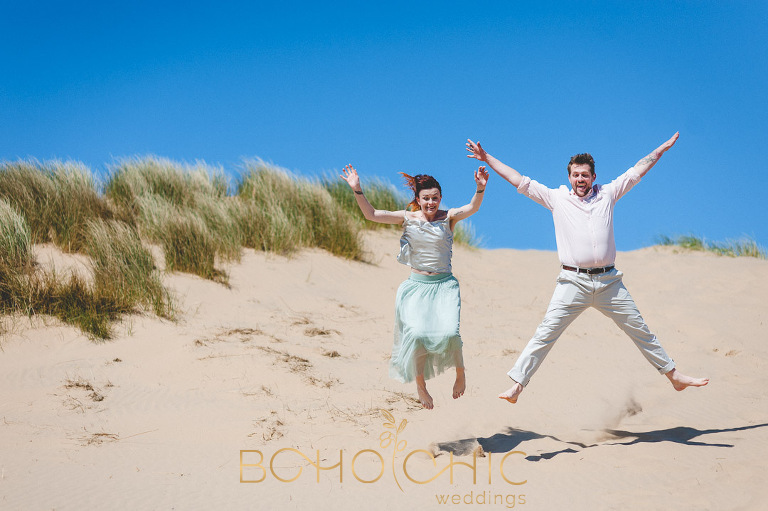 engagement photograph of a couple leaping in the air